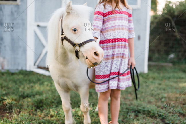 Girl standing with a white pony on a farm