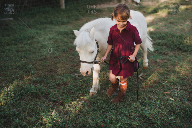 Little girl walking with a small white pony