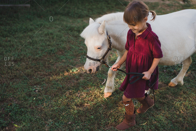 Little girl walking in a field with a white pony