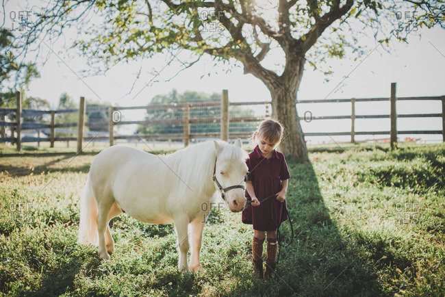 Little girl standing with a white pony in a field