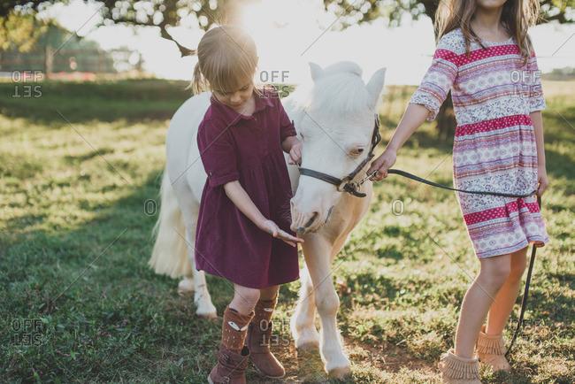 Two girls walking a white pony on a farm