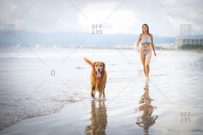Mexico- Nayarit- Young woman walking with her Golden Retriever dog at the beach