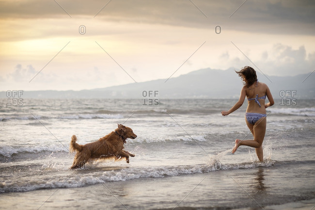 Mexico- Nayarit- Young woman in bikini playing with her Golden Retriever dog at the beach