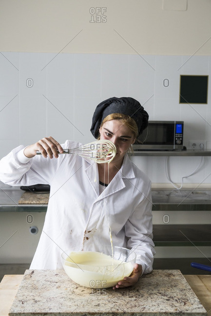 Woman checking the thickness of melted white chocolate
