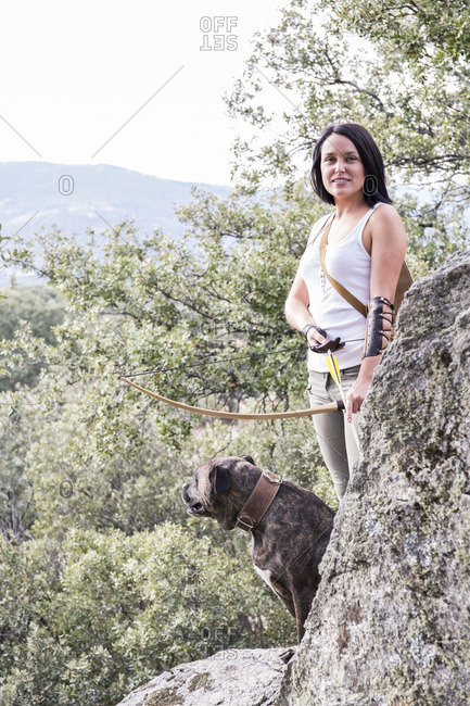 Portrait of smiling archeress with her dog in nature