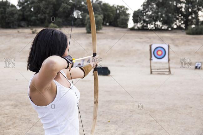 Archeress aiming at target