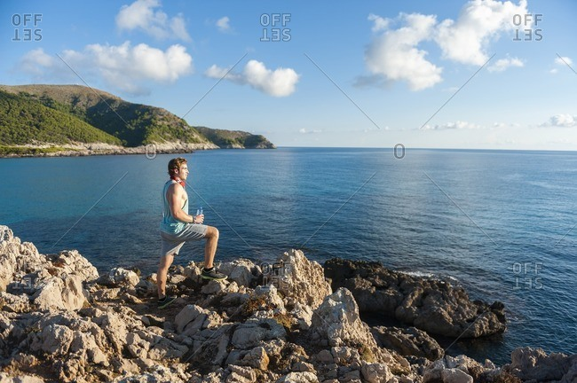 Spain- Mallorca- Sportsman standing on rocky coast in the morning