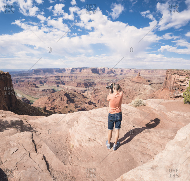 USA- Utah- Young man standing on Dead Horse Point photographing Colorado River