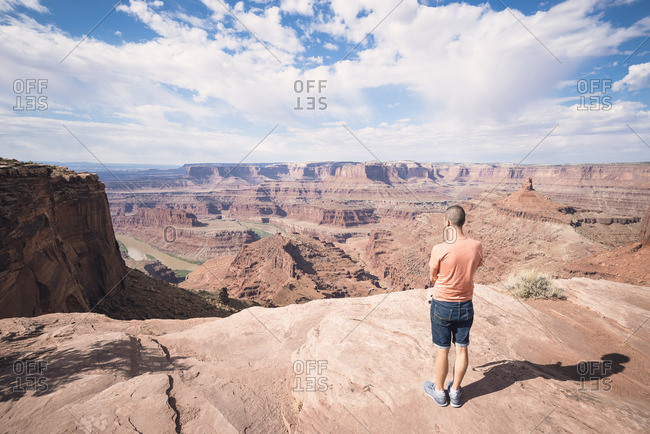USA- Utah- Young man standing on Dead Horse Point looking to Colorado River