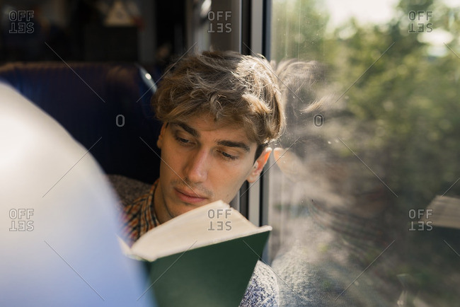 Young man reading book in a train
