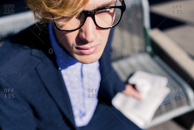 Face of young businessman at sunlight- partial view