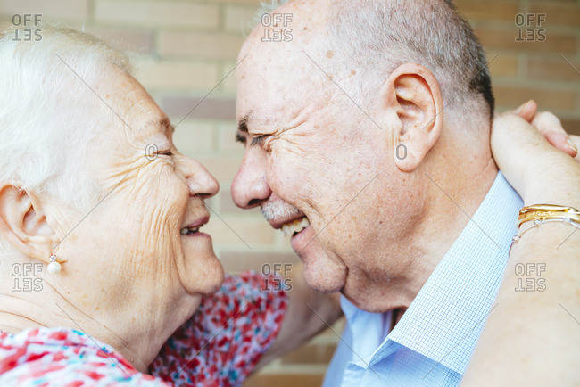 Laughing senior couple face to face