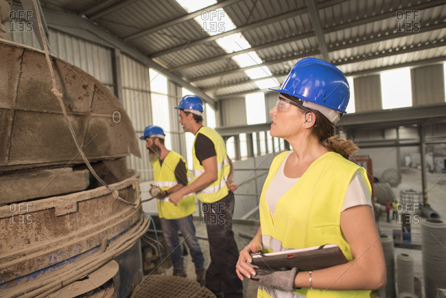 Woman standing in factory hall with workers operating giant concrete mixer