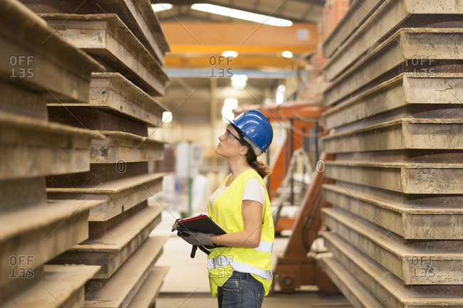 Woman looking at material in factory hall