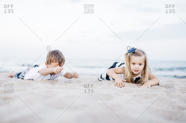 Little boy and little girl playing on the beach