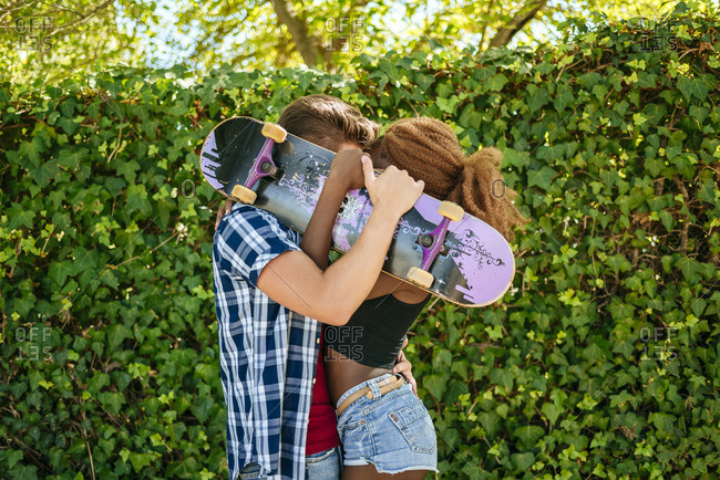 Couple kissing behind a skateboard