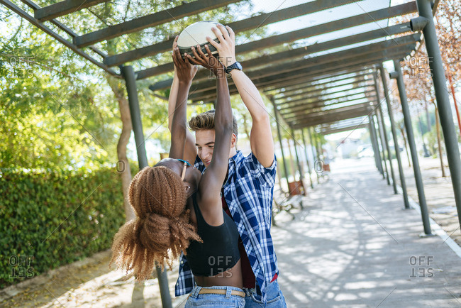 Happy young couple playing with a rugby ball