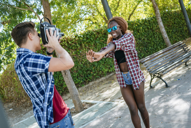 Young man filming his girlfriend with an old-fashioned camera