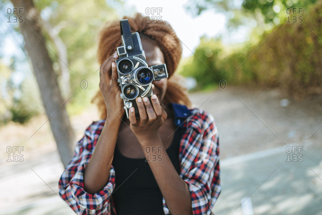 Young woman filming with an old-fashioned camera