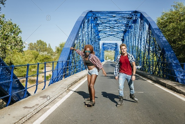 Young couple with inline skates and skateboard riding on a bridge
