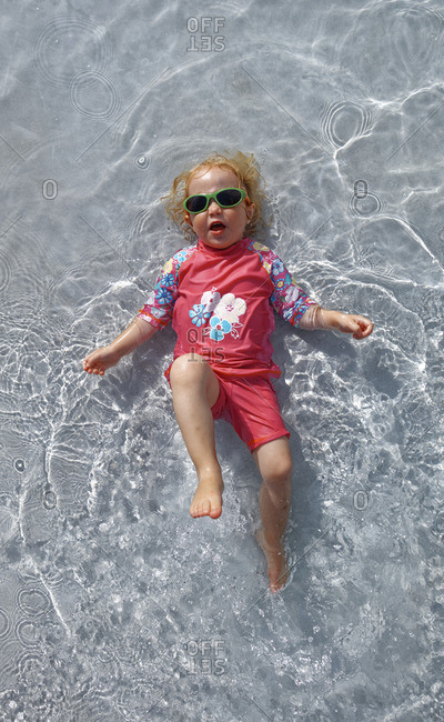 Clothed little girl with sunglasses  lying on back in water