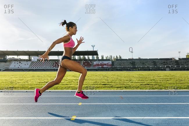 Female athlete running on racetrack