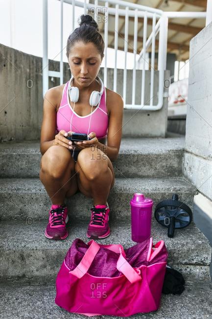 Female athlete sitting in stadium reading text message
