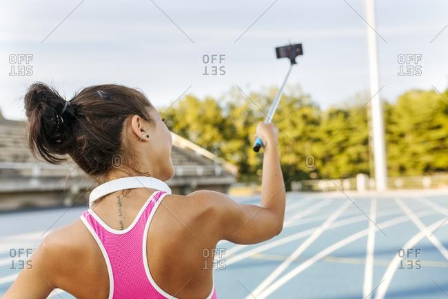 Female athlete taking selfies in stadium- holding selfie stick