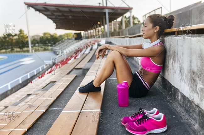 Female athlete taking a break- sitting in stadium