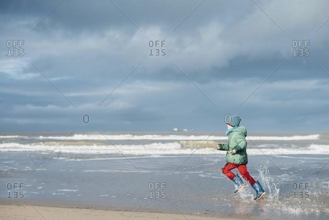 Denmark- Skagen- boy in winter clothes running on beach