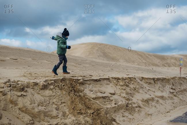 Denmark- North Jutland- boy running in wandering dunes at lighthouse Rubjerg Knude