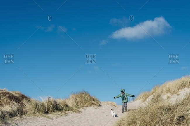 Denmark- Bulbjerg- boy in winter clothes with dog in dunes