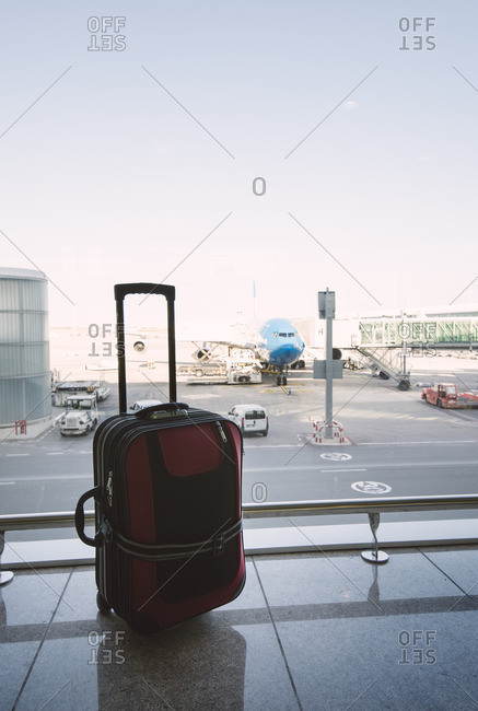 Red suitcase at airport- airplane in background