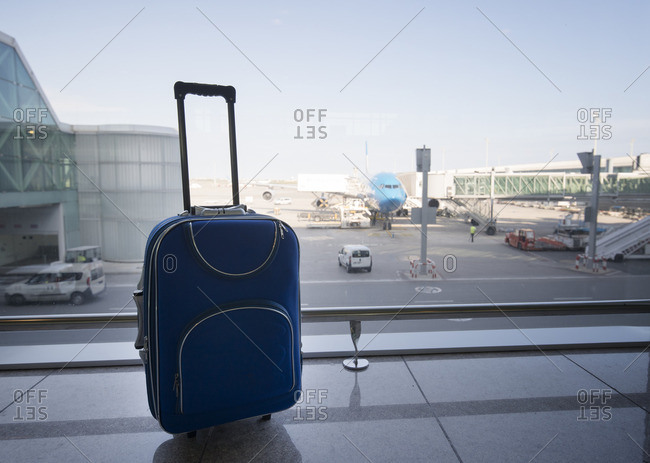 Blue suitcase at airport- airplane in background