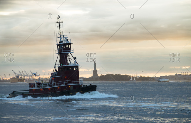 USA- New York City- tugboat on Upper New York Bay with Statue of Liberty in background