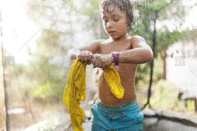 Boy standing on trampoline wringing out his wet t-shirt