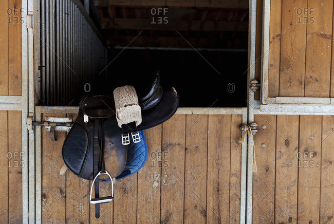 Saddle hanging on door of horse stable