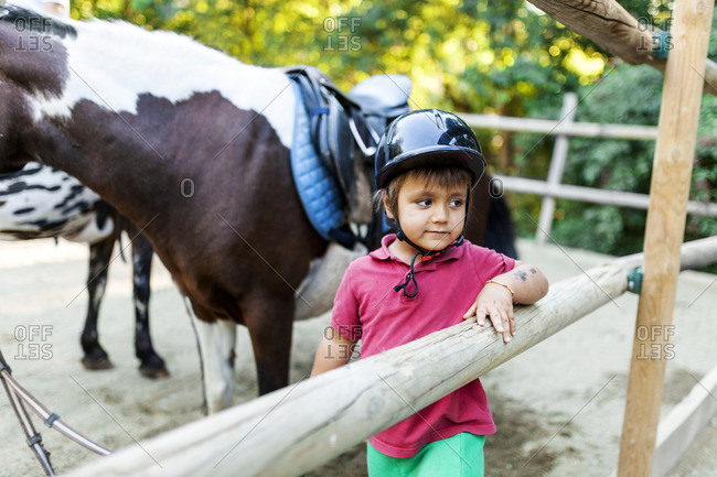 Little boy waiting to start riding lesson