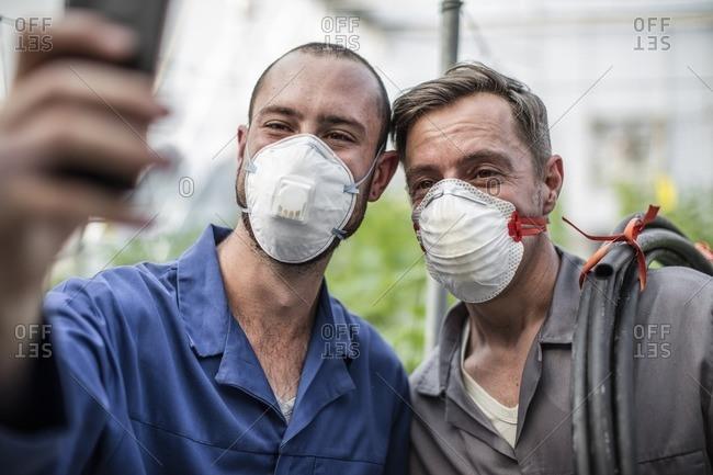 Gardeners in greenhouse taking selfie wearing face masks