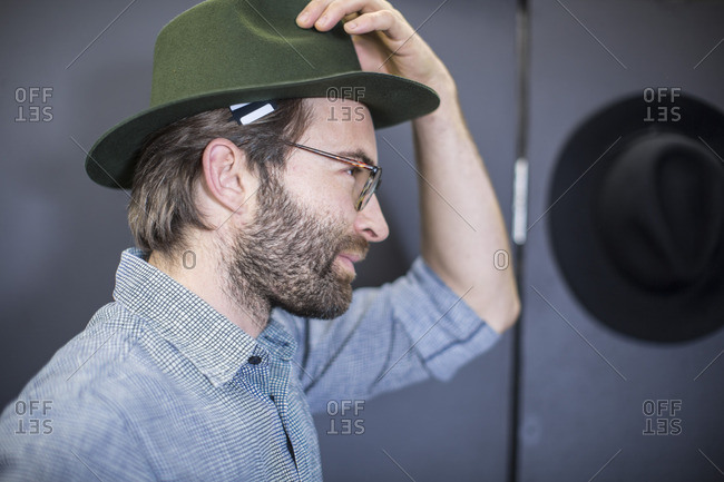 Man in shop trying on hat