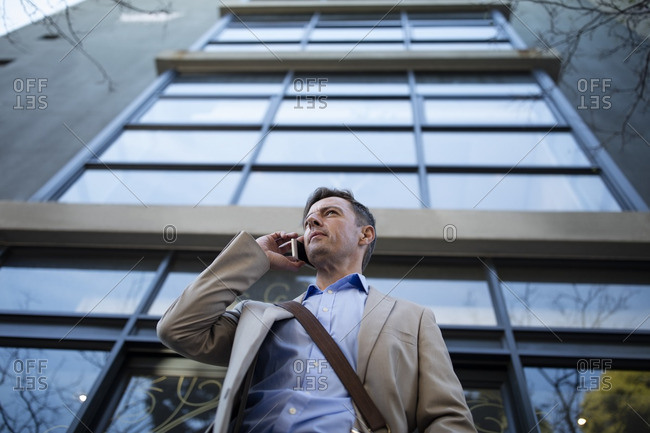 Businessman on cell phone outside building