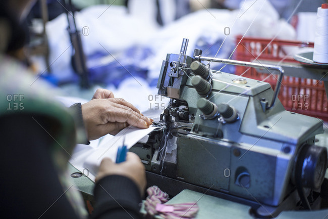 Seamstress in clothing factory sewing clothes
