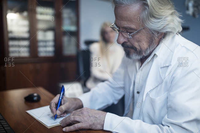Ophthalmologist writing medical record of patient