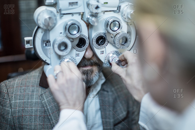 Female optometrist doing eye test with patient