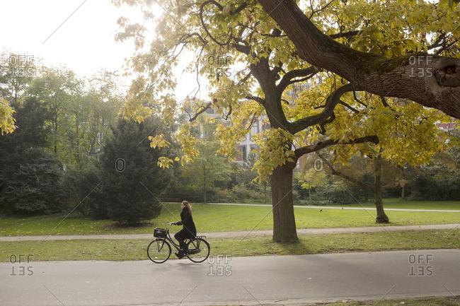 Amsterdam, Netherlands - October 14, 2016: Woman on her bike in park