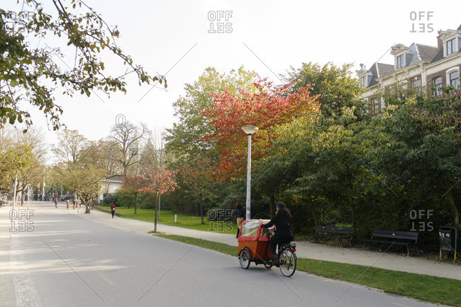 Amsterdam, Netherlands - October 14, 2016: A woman riding her bike in park