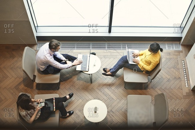 Office workers using devices in sitting area