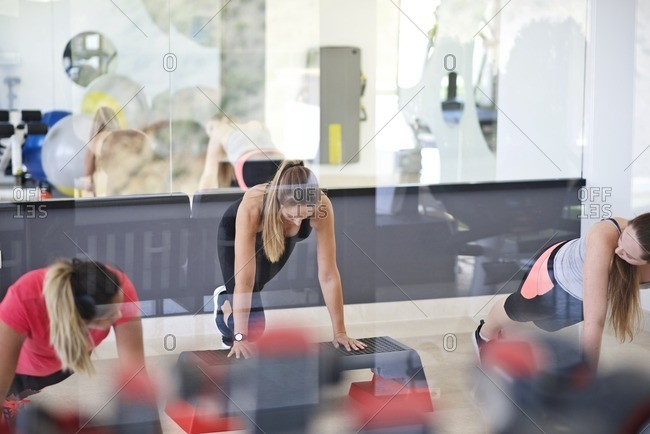 Women using step bench in workout