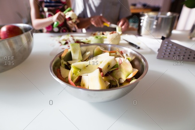 A bowl of apple peels and apple cores on a table
