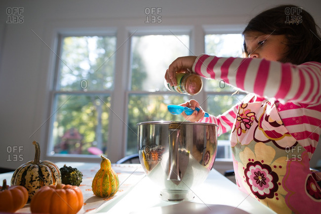 Girl adding ingredients to a measuring cup